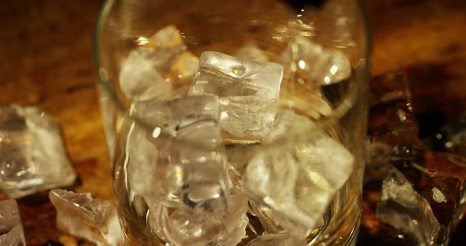 Whiskey poured into a glass with ice, in slow motion, macro shooting, on a wooden table and dark background. Concept: alcohol, spirits, for a good evening, alcohol harms health.