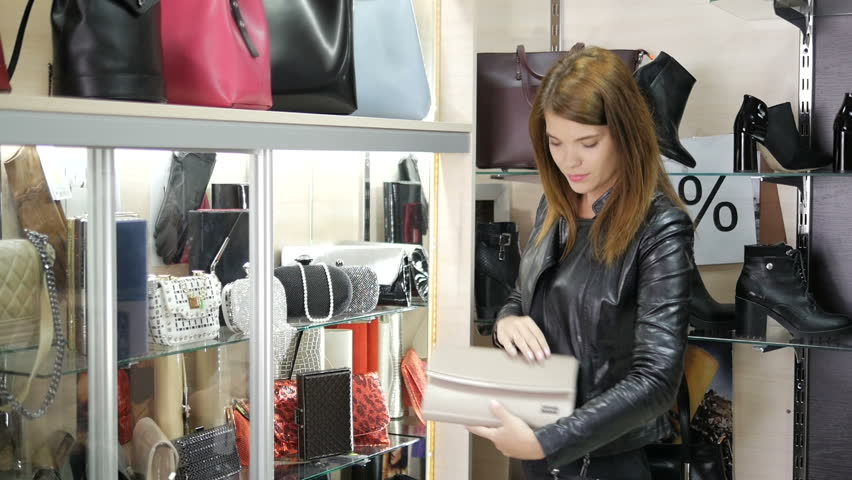 A beautiful girl is shopping at the mall and chooses a bag. | Shutterstock HD Video #26246717