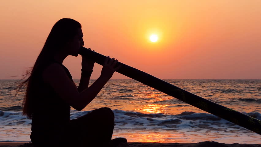 Didgeridoo playing. Male Silhouette with Didgeridu near Sea. Handsome long-haired Man with sexy body Playing Didgeridoo. Action, Australian wind instrument. Musician playing Live ethno music.