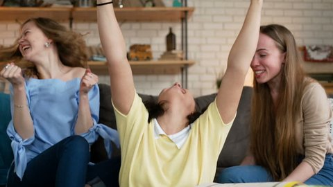 two young girl student rejoice actively for friend who received best news on telephone and became happy, they cheer and enjoy lively together, while studying and preparing for exam together at home