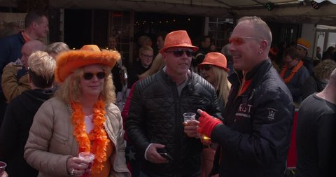EINDHOVEN, NETHERLANDS - APRIL 27, 2017: Dutch people with orange clothes drinking a beer at the free secondhand market on Kings day