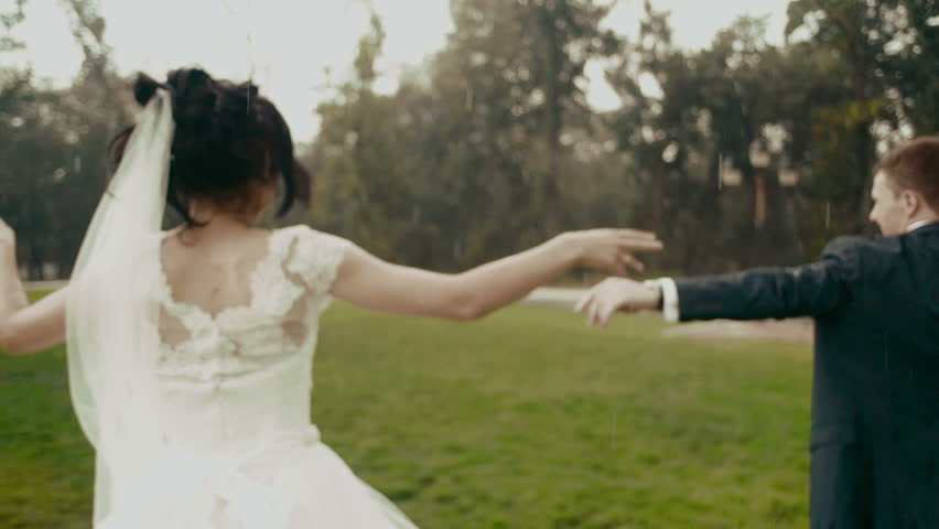 The happy newlyweds are dancing in the rain in the park during the summer.