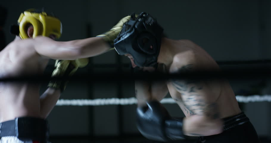 Professional sparring of two (young) partners of boxers in the ring, practice strike technique, rack, defense and endurance, in protective helmets. Concept: love sports, young boxers, love to win.