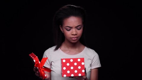 Excited young afro american woman opening gift box and looking disappointed isolated on a black background