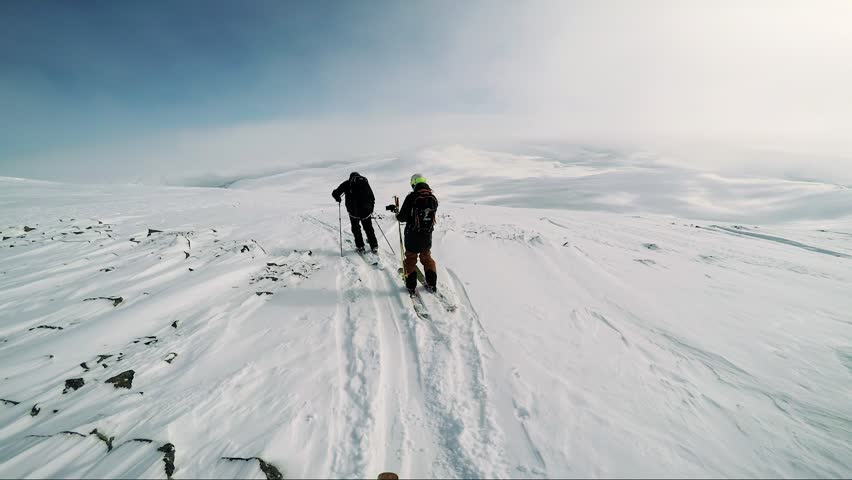 NIKKALUOKTA, SWEDEN - APRIL 22, 2017: Man skier is on the top of the mountain with friends and they get ready for skiing - sunny day - first person view | Shutterstock HD Video #26294204