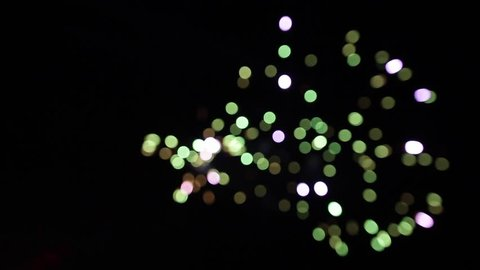 Colorful fireworks turn to multicolor bokeh lights at summer holiday night.