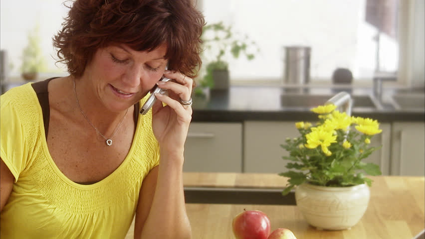 Mature woman talking on phone and using laptop