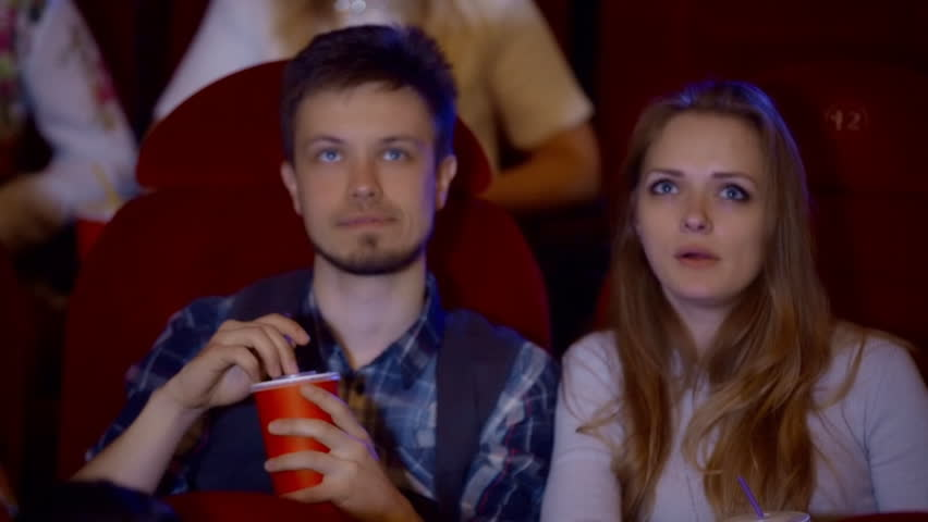 Young couple sitting in the cinema, watching movie, eating popcorn, drinking and smiling. #26333771
