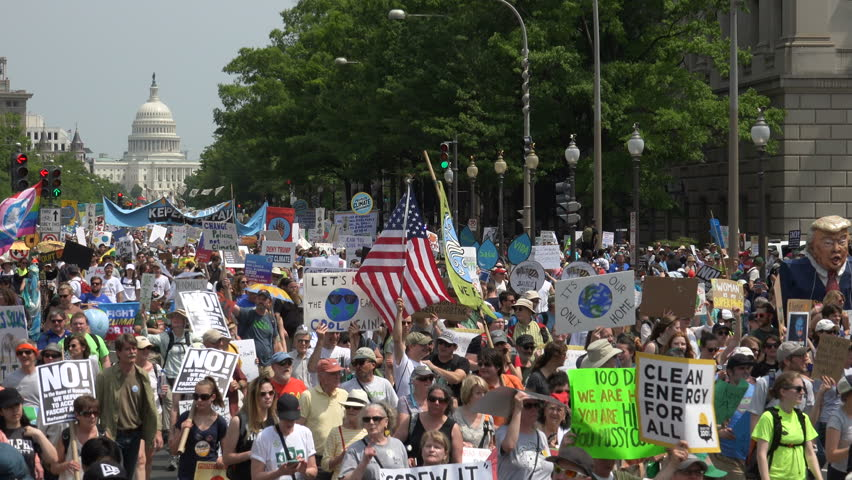 WASHINGTON, DC – APR. 29, 2017: Capitol in background, People's Climate March massive crowd protesting  Donald Trump's environmental protection rollbacks, march on Pennsylvania Ave. to White House.