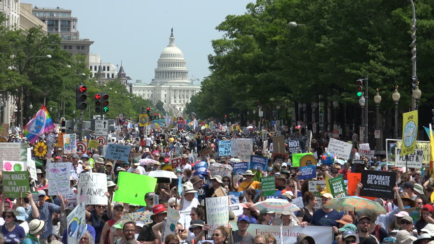 WASHINGTON, DC – APR. 29, 2017: Capitol in background, zoom out, People's Climate March huge crowd protesting  Donald Trump's environmental protection rollbacks,on Pennsylvania Avenue