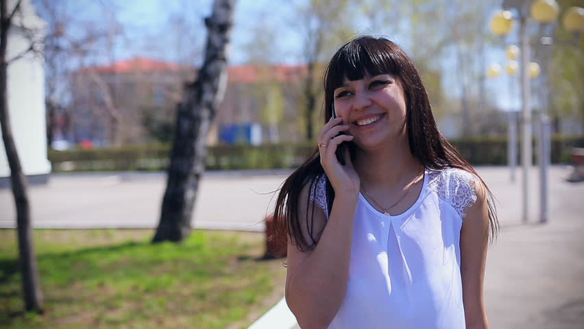 Eastern beautiful girl in a white blouse walks in the park smiling and talking on the phone | Shutterstock HD Video #26366681