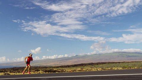 Triathlon - Triathlete man running in triathlon suit training. Male runner exercising in beautiful landscape on road on Big Island Hawaii