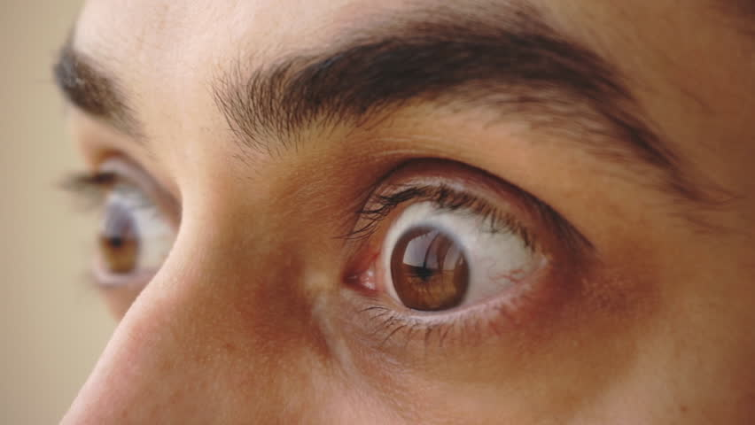 Close up of man's brown eyes looking with surprise