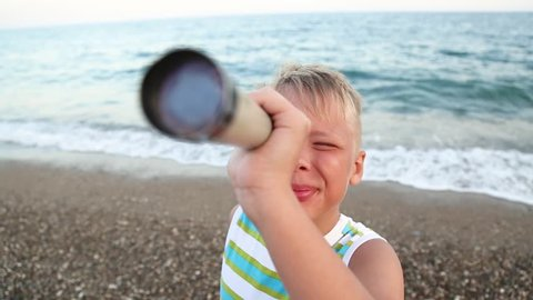 Closeup portrait of little blond child watching through spyglass at first, then looks at camera cheerfully. Kid plays spy games at beautiful blue sea horizon. Real time full hd video footage.