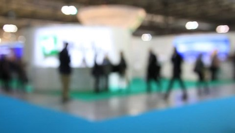 People at a trade show. Background with an intentional blur effect applied. Humans and location not recognizable.