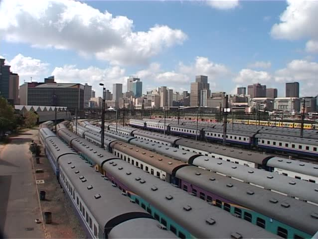 Pan across the skyline of Johannesburg and the Park Station railway yard to the Nelson Mandela Bridge.