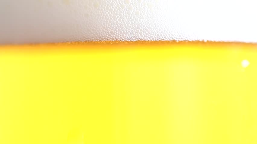 air bubbles when pouring a fresh beer into a glass goblet #26447021