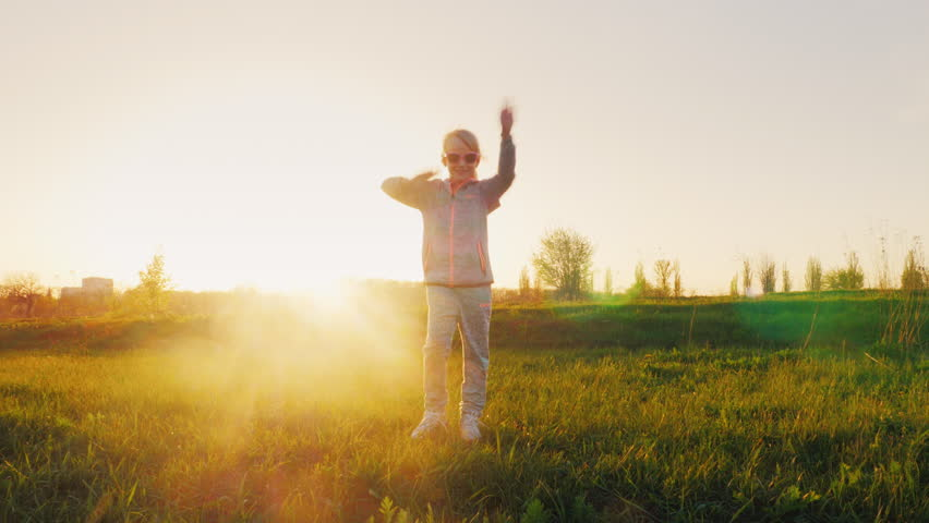 Funny girl in pink glasses and a sports suit does gymnastics. Running through the green meadow at sunset, the sun shines beautifully from behind | Shutterstock HD Video #26447891