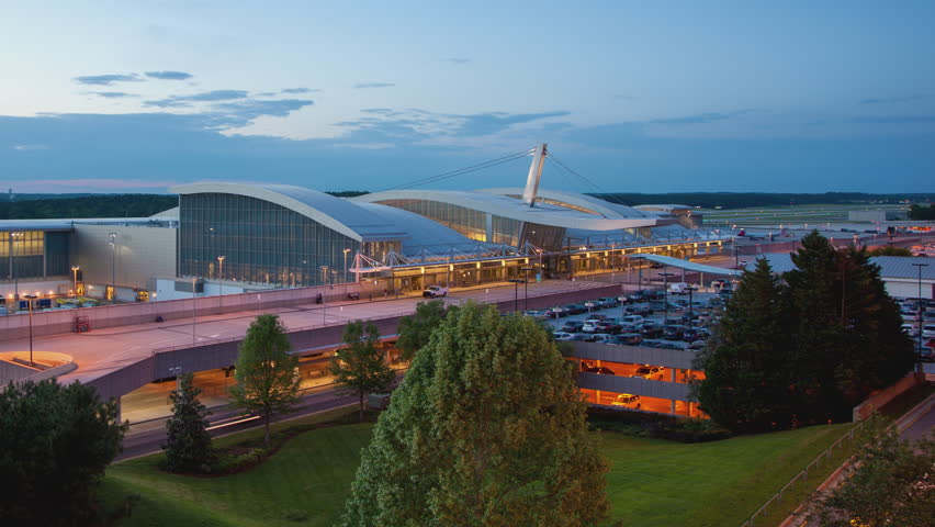 Raleigh-Durham International RDU Airport Terminal Building Exterior Timelapse with Aircraft and Vehicle Traffic Movement during Sunset into Evening