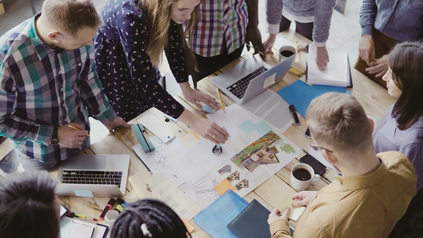Top view of young team working on architectural project. Group of mixed race people standing near table and discussing. | Shutterstock HD Video #26472734