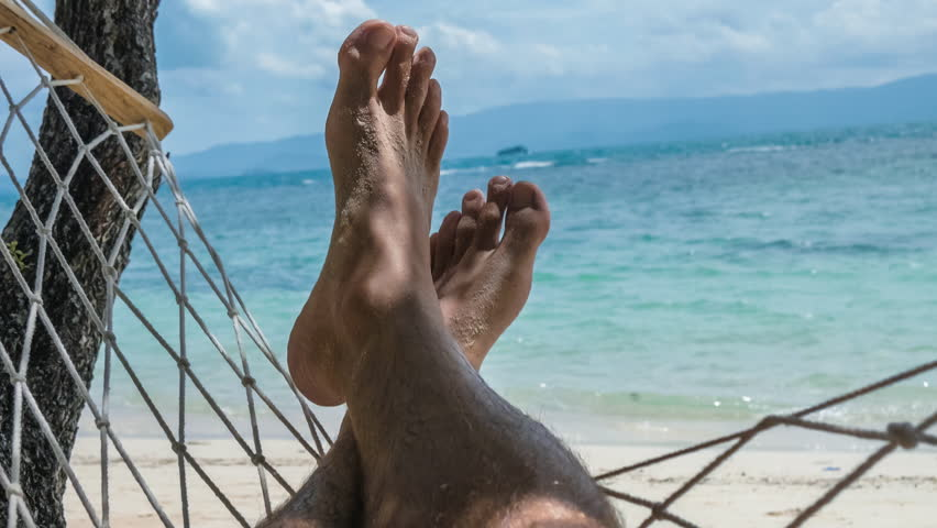 Swinging bare man feet with beach white sand swinging in a hammock on vacation in front of the blue ocean. | Shutterstock HD Video #26473241
