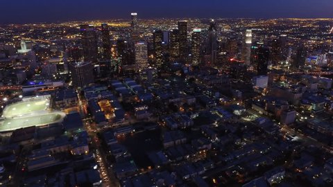 Los Angeles, California. Circa 2016. Aerial view of the Financial District. Famous downtown skyscrapers at night. Traffic passing by 110 freeway. Shot from helicopter.