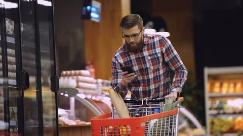 Bearded man in eyeglasses and shirt walking in supermarket with shopping trolley which looking on shopping list in the smartphone