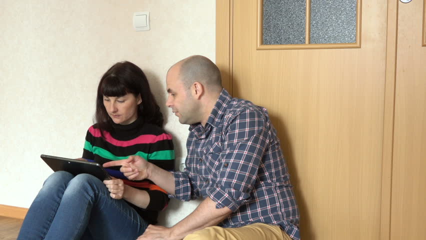 Married couple chooses the goods in the online store, sitting on floor at their new home.  Man and women talking and using tablet. Choosing a bank loan for a young couple.Quarrel