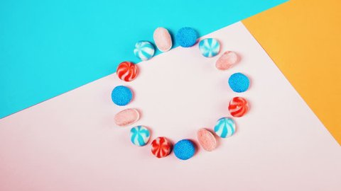 Different colorful candies moving in a circle and then disappearing on background