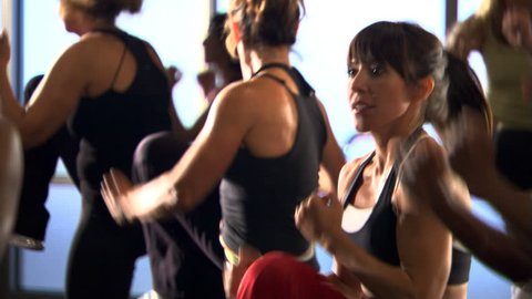 Tilt-up from legs to faces of women in a kickboxing class