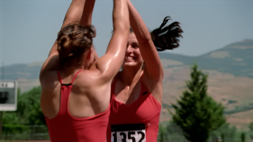 Happy female relay racers congratulating each other before turning to shake hands with rivals