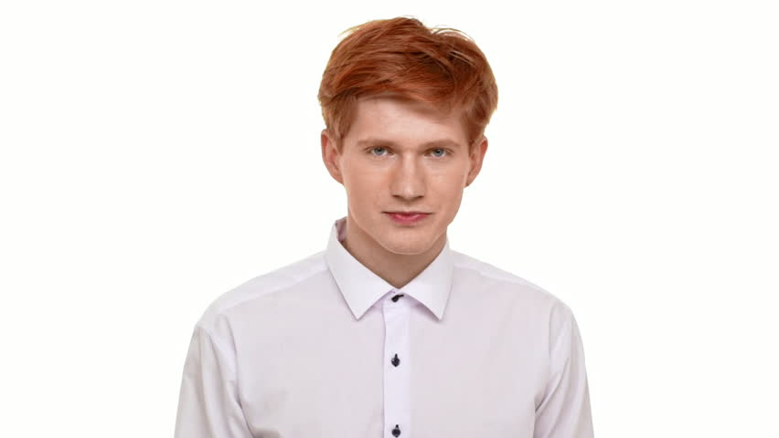 Confident young handsome ginger Caucasian young man pointing on camera on white background and smiling. Footage in slowmotion