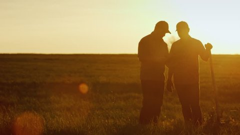 Two farmers talk in the field, use a tablet. Beautiful sunset, silhouettes of two men seen. Copyspace composition