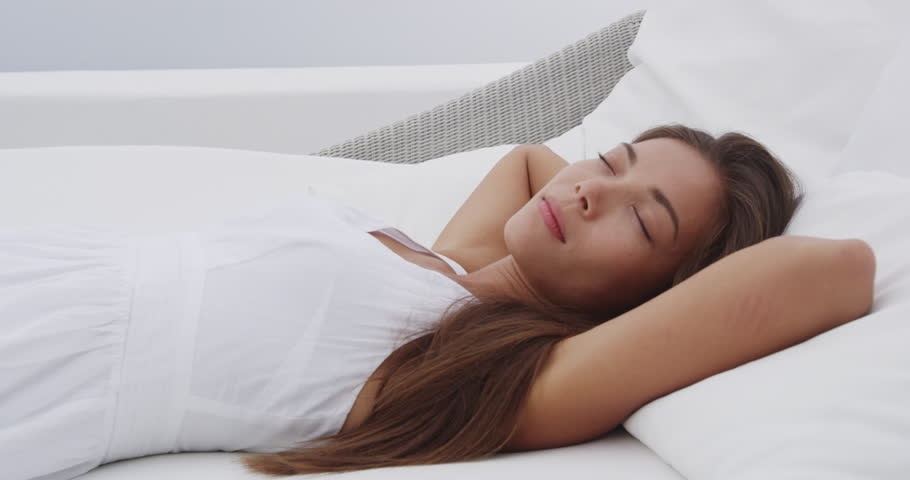 Woman relaxing sleeping beautiful and comfortable outdoor on daybed sun chair lounger with head on pillow on summer terrace enjoying sleep. RED EPIC SLOW MOTION.
