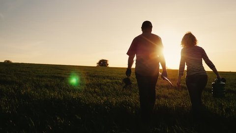 Steadicam shot: Farmers - a man and a woman walking across the field at sunset. Carry a tree seedling, a watering can and a shovel. Concept - work in the garden, volunteering, a new life