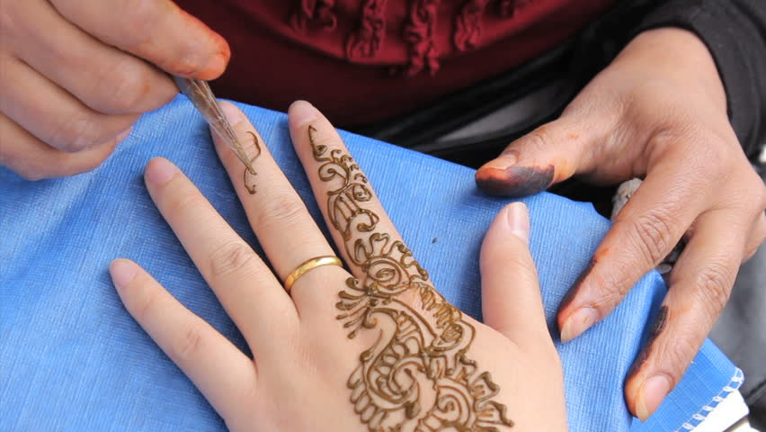 Mehndi Tattoo Hd : An indian lady does a henna tattoo on client's fingers and hand