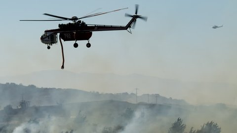 Close view of helicopter dropping fire suppressant near a canal