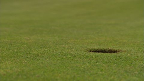 Golf ball rolling from left to drop into close-up hole at right; hand retrieves ball