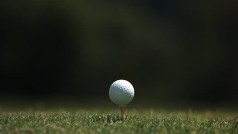 Close-up of golf ball on tee and club head striking it in ultra-slow motion