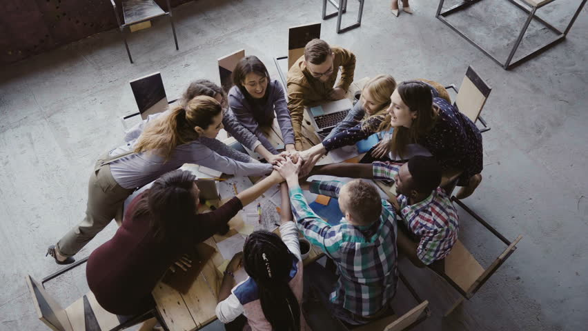 Top view of business team working at trendy loft office. Young mixed race group of people puts palm together on centre. | Shutterstock HD Video #26633884