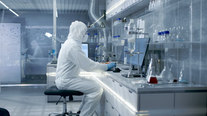 In a Secure High Level Laboratory Scientists in a Coverall Conducting a Research. Biologist Adjusts Samples in a Petri Dish with Pincers and then Examines Them Under Microscope. RED Cinema Camera. | Shutterstock HD Video #26643421