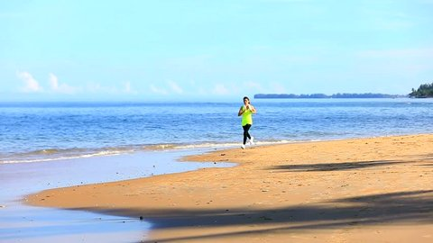 Asian woman running on tropical beach in sunlight of morning with reflect on sand taken in slow motion technique