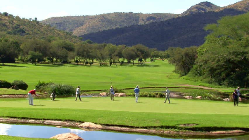 Men playing golf together on a course, South Africa