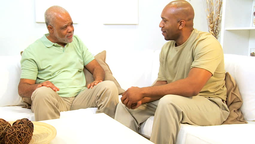 African American father and son chat together on a couch
