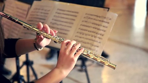 Woman Musician Plays the Flute. Flutist Professionally Playing the Flute in the Orchestra, Classic Music