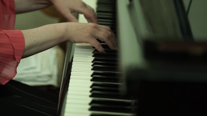 Girl's hands on the keyboard of the piano. The girl plays piano,close up piano. Hands on the white keys of the Piano Playing a Melody. Women's Hands on the keyboard, Playing the Notes Melody. | Shutterstock HD Video #26714131