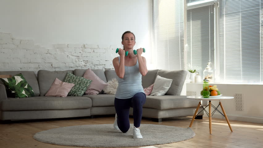 Young fit and energetic woman doing sport workout and fitness lunge exercises with weights for healthy lifestyle in living room at home during sunny day | Shutterstock HD Video #26714371
