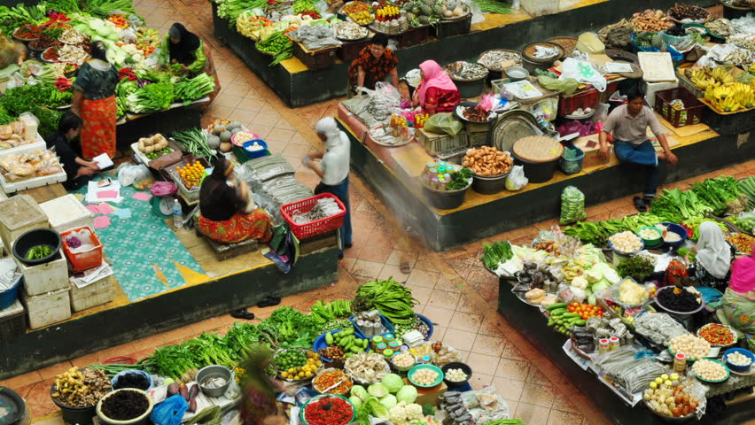 MALAYSIA - JANUARY 24: Time lapse of Muslim woman selling fresh vegetables at the traditional bazaar market Siti Khadijah Kota Bahru on January 24, 2011 in Kelantan, Malaysia.
