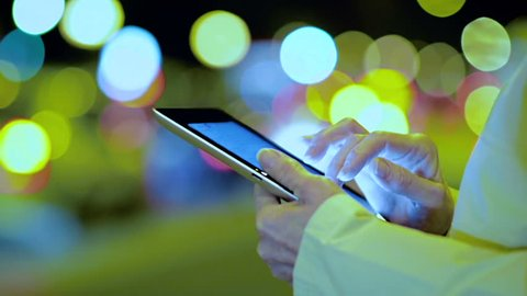 Close-Up of Female Hand Using IPad in the City in the Evening