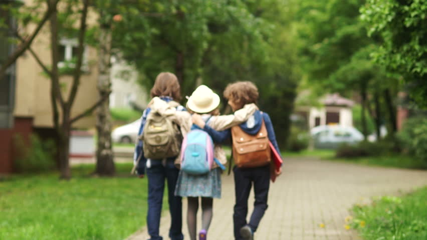 Two boys and girl are returning home after the school. The girl catches up with the boys and hugs them. School friends, childhood love, to accompany home. Friendly hugs. Going out school.